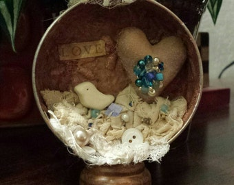 Art assemblage in a vintage candy tin. Antique lace and buttons, muslin heart and polymer clay bird. Many beads