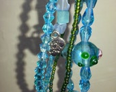 Bracelet turquoise three string with silver plated clasp.  Aqua beads and crystals and green seed beads.