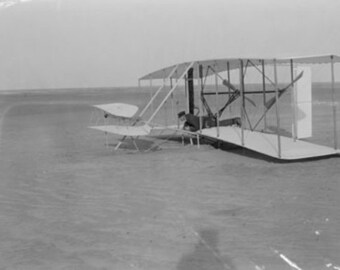 Wilbur Wright in damaged plane after unsuccesful flight Photograph (Art Prints available in multiple sizes)