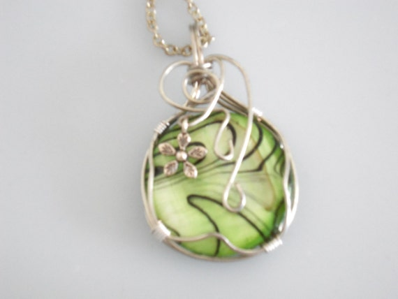 Wire wrapped pendant. Lime green & black cabochon wrapped with silver plated copper wire. Silver flower embellishment.