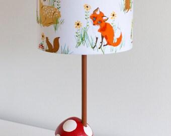 Woodland nursery toadstool lamp with woodland creatures barrel lamp shade featuring fox, deer racoon.
