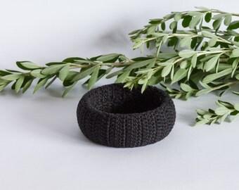 Bracelet. Black bracelet decorated with knitted threads. Black bracelet