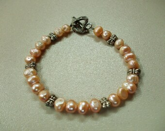 Pink pearl bracelet with butterflies.