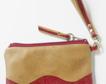 Leather clutch or wristlet, in tan bomber jacket leather with red tooled trim.
