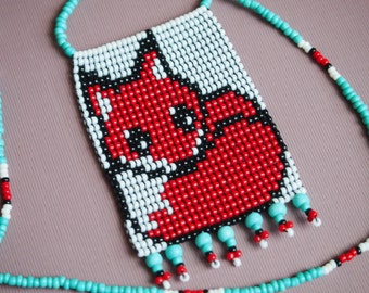 a very red, curled up fox complemented by tranquil turquoise. cute beadwork fox pendant on turquoise bead strand necklace.