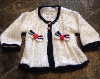 Baby girl's knitted cardigan with navy blue edging and pretty bows with 2 button fastening