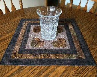Quilted square batik table topper in shades of brown with hand quilting and applique