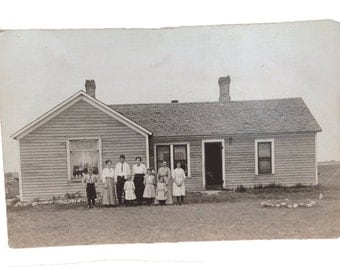 Postcard of a family standing in front of a house-black and white (P37)