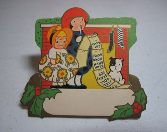 Colorful unused die cut gold gilded 1920's Dennison christmas place card kids next to fireplace with their dog writing wish list holly berry