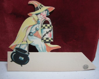 1920's-30's unused die cut halloween place card young witch carrying black cauldron and black bat decorated lantern The Line Unique