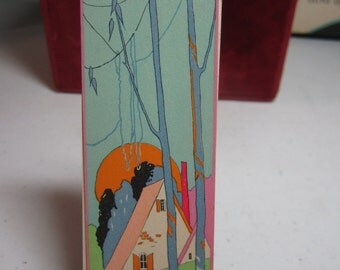 1920's Gibson bridge tally card brightly colored art deco design of a cottage surrounded by stylized deco trees, flowers sun in the distance