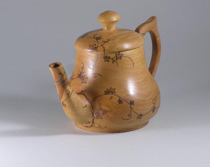 Wood teapot with a vine design