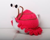 Knitted pink snail tea cosy with frilly bottom. Washable fits 1 litre teapot. Available with or without teapot.