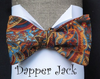 "Paisley Print Bow Tie in Autumn Shades, on an adjustable band, will fit up to a 19.5"" neck size. Self tie option no longer available."