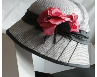A handmade silvery grey fine straw cloche hat with pleated detail, trimmed with handmade silk pink roses