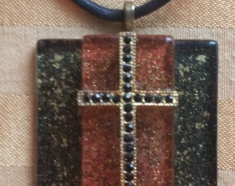 Three-tiered glass pendant with a gold and black cross