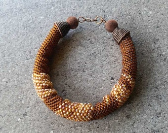 yelMulti-coloured yellow and brown small beads bracelet with a metal fastening.