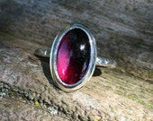 Scarred sterling ring with oval bezel set two tone deep pink tourmaline cabochon