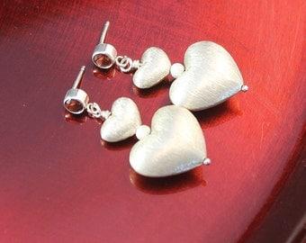 The Gabbi Double Heart Earrings - Bali Silver Brushed Puffed Heart Earrings with Garnet Stud Posts in Sterling