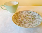 Mid century tea cup and saucer, no maker noted. Cute sweet floral seafoam green pattern. In good condition has gold trim.