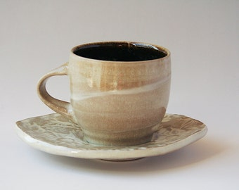 Coffee cup with leaf shaped saucer & white flannel flower design
