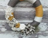 Handmade yarn wrapped wreath. Grey, mustard yellow and cream roses in burlap and felt fabric. Fun chevron print burlap daisy.