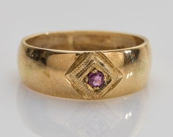 18 ct solid gold ring with a small red semi-precious stone