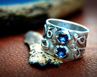Woman's sterling silver ring with blue topaz CZ stones and swirly design around the wide band. One of a kind, different and funky. #WR102