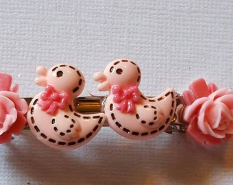 2 inch barrette with 4 resin pieces, 2 adorable pink duckies with hot pink ribbons hugged by 2-tone pink resin flowers.