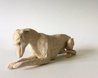 Ceramic greyhound lying down dog sculpture in white clay