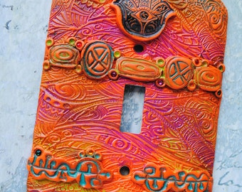 Orange Hamsa switch plate, polymer clay in orange, yellow, blue, green,