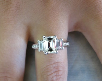 14K white gold past, present, future emerald cut engagement ring.