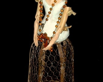 Ceramic hand made Santos doll on wire cage