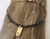 Black spinel and gold Om charm bracelet. Dainty gemstone yoga bracelet. Minimalist bracelet.