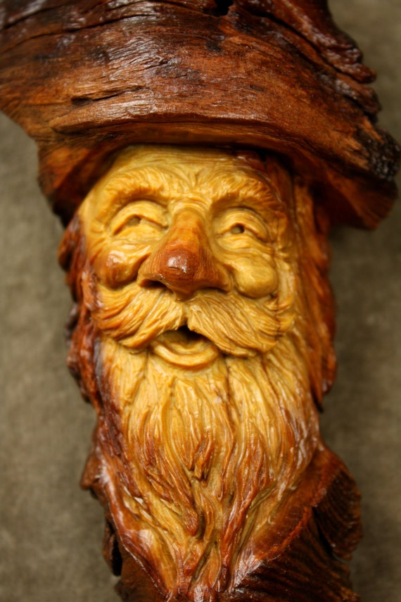 A carved face wood carving of spirit wizard tree