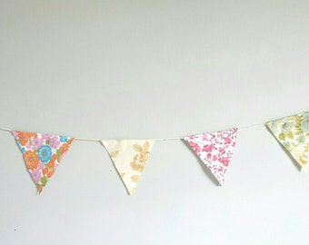 Mini bunting made from vintage fabric on cotton string for decorating rooms, walls, bookshelves, beds, parties, party favours. Free postage