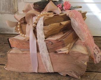 Distressed tattered book bundle stack Romantic vintage embellished w/ antique baby shoes pearl lace shelf vignette decor anita spero design
