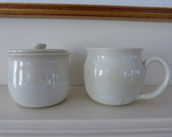 Creamy white sugar bowl and creamer set.