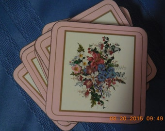 Set of 8 vintage coasters with cork back and pink flowers on the front.