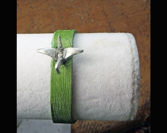 green leather wrist cuff with a Japanese crane in flight