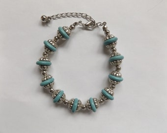 Turquoise colored beads with silver colored metal