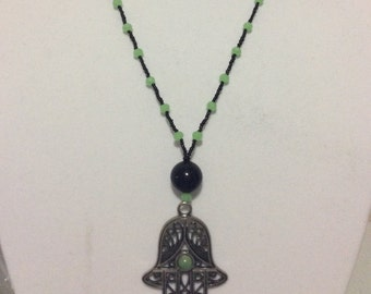 Green and black necklace with beautifull amulet