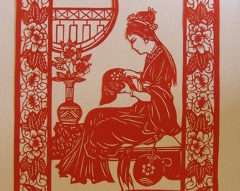 Chinese Papercut of a woman making an embroidery