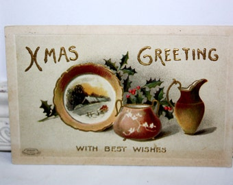 Vintage Christmas Postcard Embossed of a golden plate, pot and pitcher with green holly and red berried by Davidson Bros series 1414X 1910