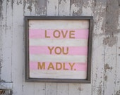 pink and white striped love you madly sign