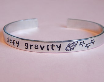 Defy Gravity, Wicked Inspired Hand Stamped Aluminum Bracelet - Gift Under 20