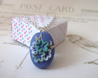 Handmade polymer clay flower pendant, purple, with green and white flowers,