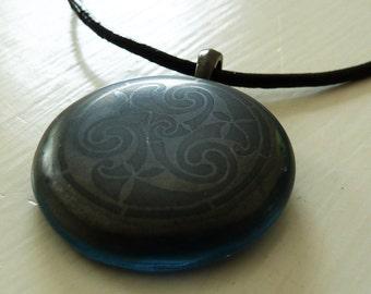 Blue, black & grey fused glass pendant with celtic spiral triskele pattern
