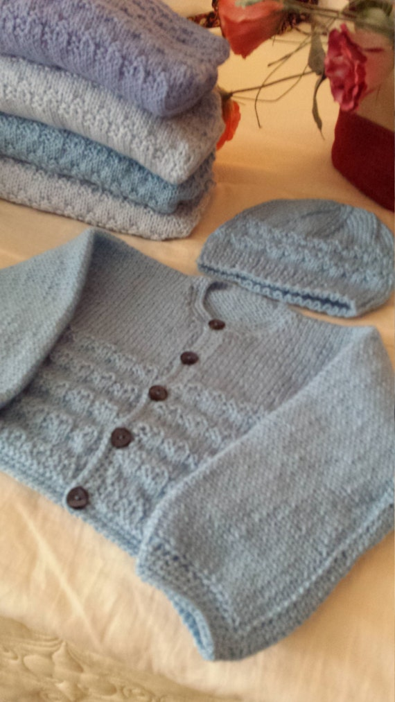 Baby sweaters and hats hand knitted by aunt Corry
