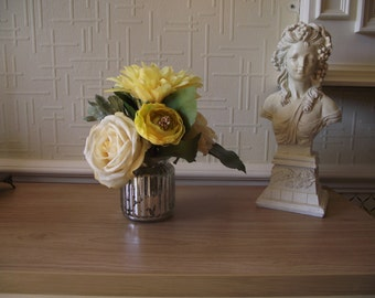Artificial flower arrangement of yellow roses, dahlia and ranunculus in silvered glass vase set in acrylic water